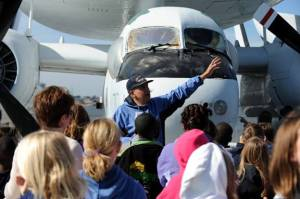 Volunteer and former naval aircrewman Hank Siefried talks to 5th graders about the E-1 Tracer early warning aircraft.