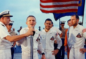 Frank Borman addresses the crew of USS Yorktown, Bill Anders and Jim Lovell to the right.