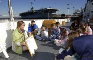 Marine science instructor conducts class on USCG Ingham with USS Yorktown (CV-10) in background.