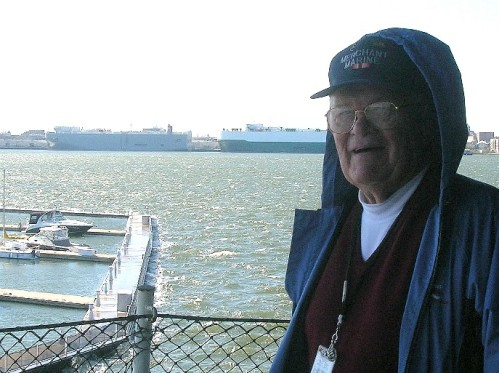 Volunteer Bob Barkus with a windy, choppy Charleston harbor in the background along with a few merchant ships at berth.