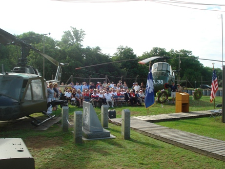 Veterans and families seated between two Vietnam era helicopters, the UH-1 Huey and the UH-34 Seahorse.