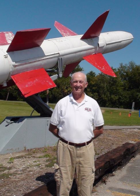 Volunteer Larry Moran in front of a Talos missile.